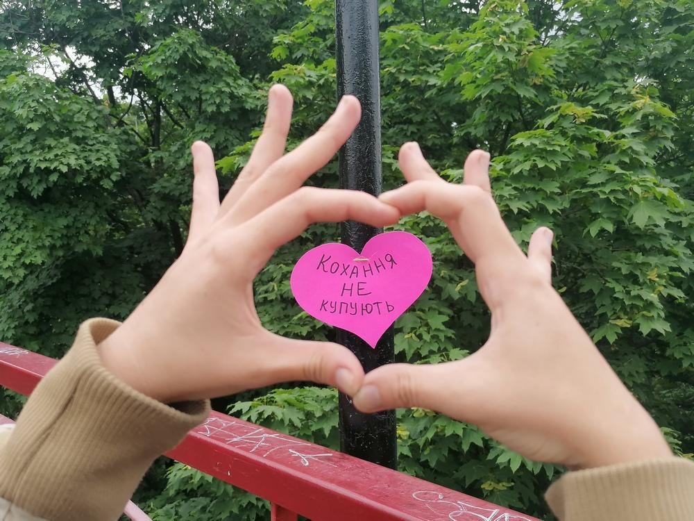Жінка прикрашає Міст кохання, Київ, 28 червня 2021 року. Флешмоб про згоду на секс до 25-ї річниці Конституції України